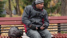 Hombre borracho que sostiene la botella vacía de cerveza, expectoración, maneras pobres, degradación almacen de video