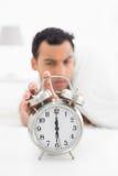Hombre borroso en mano que extiende de la cama al despertador foto de archivo libre de regalías