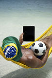 Hombre brasileño que se relaja con la hamaca de la tableta y de la playa del fútbol Fotos de archivo libres de regalías