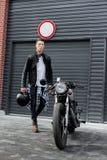 Hombre brutal cerca de su moto de la aduana del corredor del café Fotografía de archivo