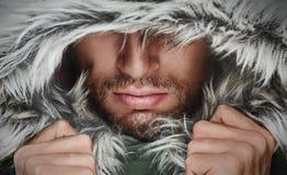 Hombre brutal con las cerdas de la barba e invierno encapuchado Imágenes de archivo libres de regalías