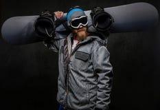 Hombre brutal con una barba roja que lleva una tenencia de equipo completa una snowboard en su hombro, aislado en un oscuro textu fotos de archivo