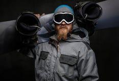 Hombre brutal con una barba roja que lleva una tenencia de equipo completa una snowboard en su hombro, aislado en un oscuro textu foto de archivo