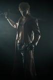 Hombre brutal con una espada aislada en negro Imagen de archivo