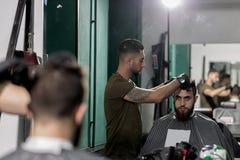 Hombre brutal en una peluquería de caballeros El peluquero cepilla sus pelos en frente el espejo fotos de archivo libres de regalías