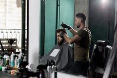 Hombre brutal en una peluquería de caballeros El peluquero cepilla sus pelos en frente el espejo foto de archivo