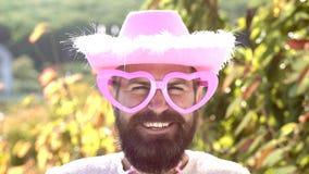 Hombre cómico con las gafas de sol divertidas del rosa del inconformista y sombrero rosado cómico Hombre loco barbudo que mira la metrajes