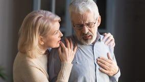 Hombre cabelludo gris que toca el pecho, teniendo ataque del corazón, apoyo de la mujer imágenes de archivo libres de regalías