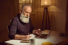 Hombre cabelludo que trabaja en casa usando los dispositivos y el cuaderno digitales Fotografía de archivo