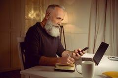 Hombre cabelludo que trabaja en casa usando los dispositivos y el cuaderno digitales Imagen de archivo libre de regalías