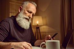 Hombre cabelludo que trabaja en casa usando los dispositivos y el cuaderno digitales Fotos de archivo libres de regalías