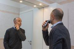 Hombre calvo con la camisa y el suéter que afeitan su barba con la maquinilla de afeitar eléctrica y el espejo Foto de archivo libre de regalías