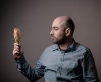 Hombre calvo confuso con el cepillo de pelo Imágenes de archivo libres de regalías