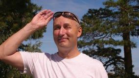 Hombre calvo en gafas de sol que goza del bosque conífero en árboles y fondo del cielo metrajes