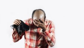 Hombre calvo que cubre su cara en la vergüenza que sostiene su peluca en el fondo blanco con el espacio para el texto imagen de archivo libre de regalías