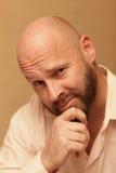 Hombre calvo que frota su barbilla fotografía de archivo libre de regalías