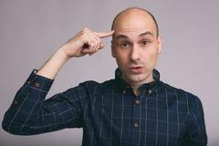 Hombre calvo que piensa con el finger en la cabeza Fotografía de archivo