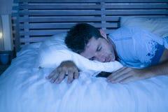 Hombre cansado atractivo en caer de la cama dormido mientras que usa el teléfono móvil todavía que sostiene el celular en su mano fotografía de archivo