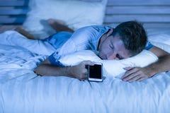 Hombre cansado atractivo en caer de la cama dormido mientras que usa el teléfono móvil todavía que sostiene el celular en su mano fotos de archivo libres de regalías