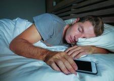 Hombre cansado atractivo y hermoso en su 30s o 40s en cama que duerme pacífico y relajado en la noche que sostiene el teléfono mó imagen de archivo