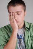 Hombre cansado joven, arropando su cara con su mano Fotografía de archivo