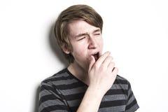 Hombre cansado joven derecho que bosteza y que estira Fotografía de archivo