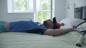 Hombre cansado joven que cae en la estafa de la tenencia de la cama después de jugar a tenis en una habitación cómoda Forma de vi almacen de video