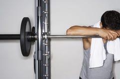 Hombre cansado que descansa sobre Barbell en el gimnasio Imagen de archivo
