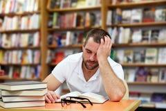 Hombre cansado que duerme en la biblioteca Foto de archivo