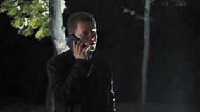 Hombre cansado que habla en el teléfono en el parque de la noche iluminado con la iluminación luminosa almacen de video
