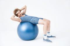 Hombre cansado que se encrespa para arriba en bola del ejercicio El parecer agotado Imágenes de archivo libres de regalías