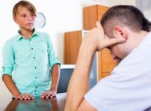 Hombre cansado y adolescente frustrado Imagen de archivo libre de regalías