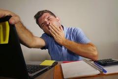Hombre cansado y agotado soñoliento que trabaja en el bostezo del ordenador portátil cansado y trabajado demasiado en oficina y s fotografía de archivo libre de regalías