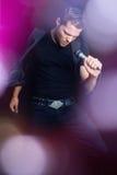 Hombre cantante en luces Imagen de archivo