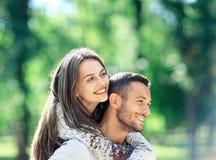 Hombre cariñoso y mujer de los pares que se divierten que lleva a cuestas en parque foto de archivo libre de regalías