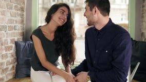 Hombre cariñoso y mujer que llevan a cabo las manos en café y la sonrisa Amantes románticos felices de los pares que hablan y que almacen de metraje de vídeo