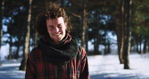 Hombre carismático de invierno que disfruta del tiempo en el medio de bosque nevoso delante de la sonrisa de la cámara grande él  almacen de metraje de vídeo