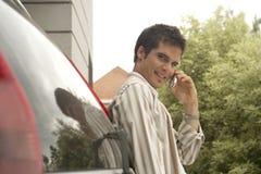 Hombre casero de la tecnología con el teléfono celular que se reclina sobre el coche Imagen de archivo
