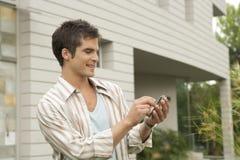 Hombre casero de la tecnología que usa un teléfono celular en jardín de la oficina Foto de archivo libre de regalías
