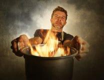 Hombre casero sucio atractivo y chocado joven del cocinero con el delantal que celebra cocinar el pote en el fuego que quema la c fotos de archivo