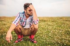 Hombre casual agachado en un pensamiento del campo de hierba Foto de archivo libre de regalías