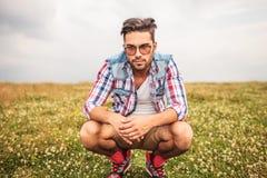 Hombre casual agachado serio en un campo de la hierba Imagenes de archivo