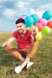 Hombre casual asentado con la victoria de las demostraciones de los globos imagen de archivo libre de regalías