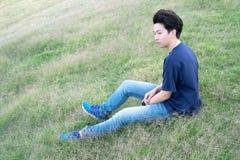 Hombre CASUAL asiático que se sienta en un fondo de la opinión del prado Retrato del COREANO joven contra fondo del prado foto de archivo libre de regalías