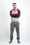 Hombre casual barbudo feliz joven en ropa de deportes con las manos cruzadas Foto de archivo libre de regalías