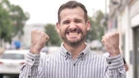 Hombre casual de la barba que celebra el éxito al aire libre almacen de metraje de vídeo