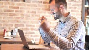 Hombre casual de la barba que celebra en el ordenador portátil en lugar del desván metrajes