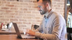 Hombre casual de la barba que trabaja en el ordenador portátil en lugar del desván almacen de metraje de vídeo