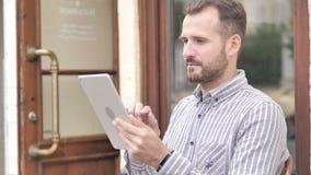 Hombre casual de la barba usando la tableta al aire libre almacen de metraje de vídeo