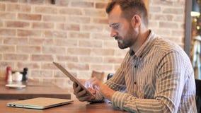 Hombre casual de la barba usando la tableta mientras que se sienta al aire libre almacen de video